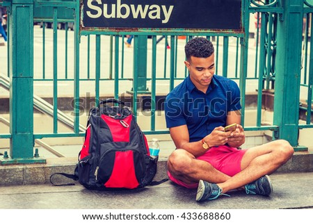 African American college student traveling, studying in New York, wearing blue short sleeve shirt, red shorts, sneakers, bag with bottle water on ground, sitting on street by Subway sign, texting.