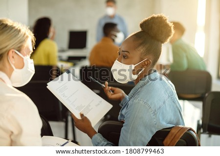 African American college student with a face mask talking to her friend about exam results in lecture hall.