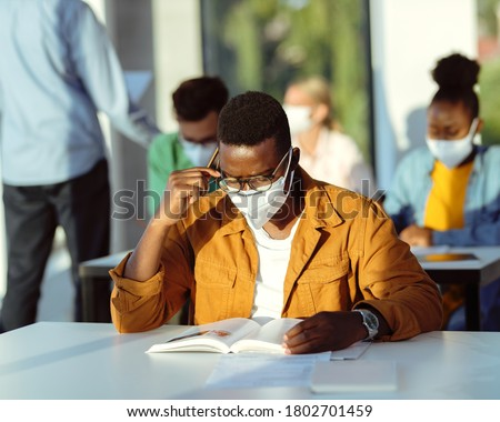 African American college student with face mask reading a book while learning in the classroom.
