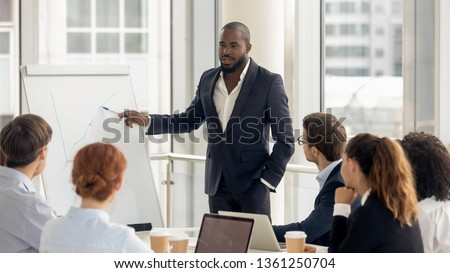 African american conference speaker coach talk to audience give presentation on flipchart to employees group, black trainer manager speaking training diverse corporate team at office meeting seminar