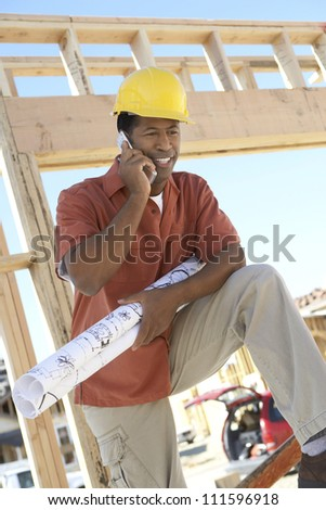 African American contractor holding blueprint while on a call