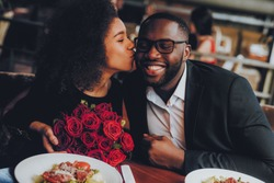 African American Couple Dating in Restaurant. Romantic Couple in Love Dating. Cutel Man and Girl in a Restaurant Making Order. Romantic Concept. Girl Kissing Man. Bouquet of Flowers. Red Roses.