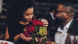 African American Couple Dating in Restaurant. Romantic Couple in Love Dating. Cutel Man and Girl in a Restaurant Making Order. Romantic Concept. Man Giving Bouquet of Flowers. Red Roses.