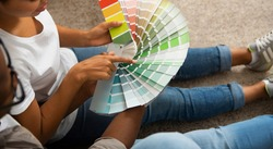 African american couple discuss in what color they will paint wall in new apartment, panorama