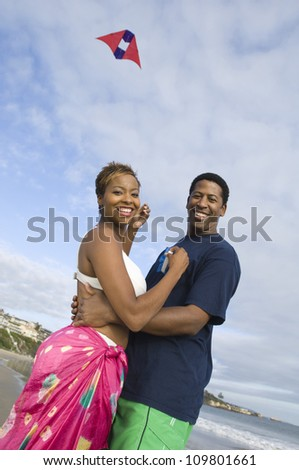 African American couple embracing while flying kite on the beach