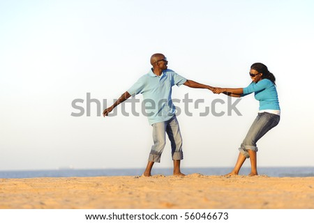 African American couple hand in hand on the beach