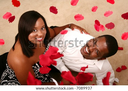 african american couple holding each other looking up to the camera with falling rose petal