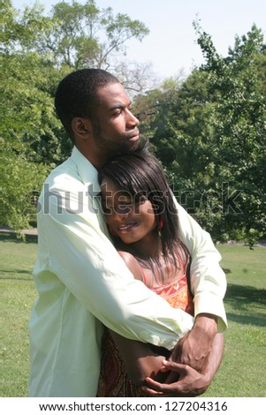 African American couple in a park with a gentle hug