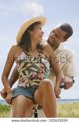 African American couple on bicycle at beach