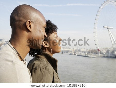 African american couple on Westminster Bridge looking at London's skyline, smiling.