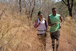 african american couple running on trail in natural forest