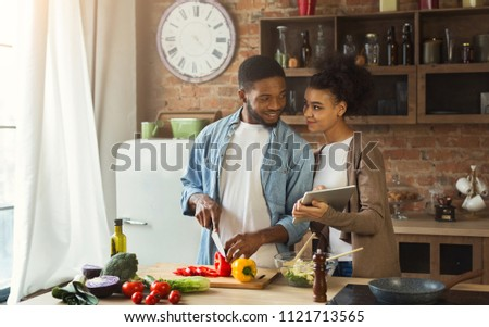 African-american couple searching for recipe using digital tablet computer in kitchen