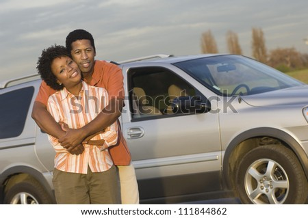 African American couple standing in front a car
