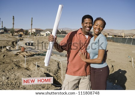 African American couple with blueprint at construction site