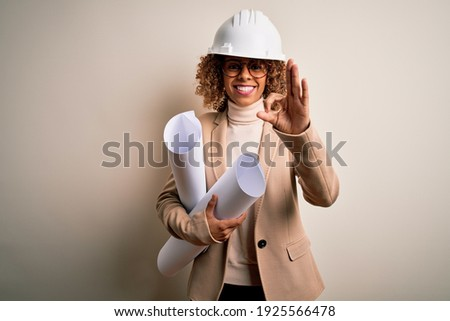 African american curly architect woman wearing safety helmet and glasses holding blueprints doing ok sign with fingers, excellent symbol Stock photo ©