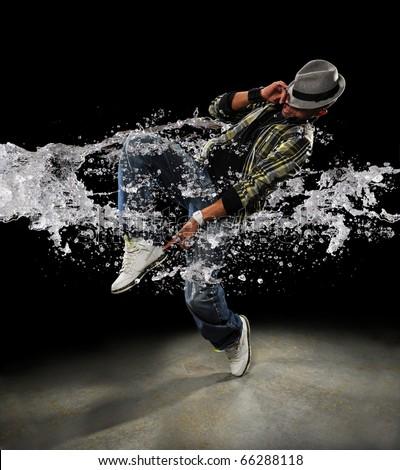 African American dancer dancing with water splash over dark background - stock photo