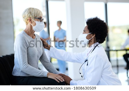 African American doctor consoling her mature patient in waiting room at medical clinic. Both of them are wearing protective face masks.