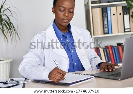 African american doctor gp therapist wear white coat, stethoscope writing medical records in notebook while using laptop computer browsing internet or watching webinar training sitting at work desk. Photo stock ©