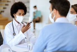African American doctor having an appointment with a couple and wearing protective face mask while communicating with them at doctor's office.