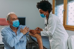 African american doctor injecting a vaccine into the patient's arm.