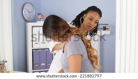 African American doctor listening to heart and lungs of Asian patient