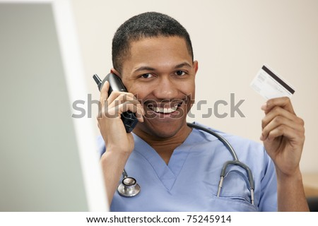 African American doctor on the phone sitting at the computer holding up his credit card