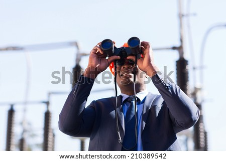 african american electrical manager using binoculars looking at substation #210389542