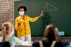 African American elementary school teacher holding mathematics class and wearing protective face mask due to coronavirus pandemic.