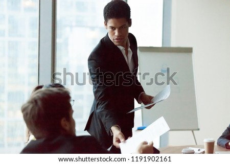 African American employee share handout material to colleagues at company meeting in office, team leader or presenter give printed plan or work results, making flipchart presentation at briefing