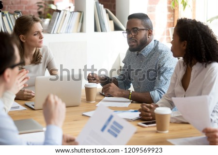 African American employee talk at briefing expressing point of view, multiracial millennial workers brainstorm in boardroom discussing project report, diverse colleagues negotiate at business meeting