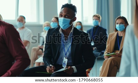 African american entrepreneur asks question on education forum business seminar of corporate company. Diversity of business people. Presentation. Health care. Virus protection.