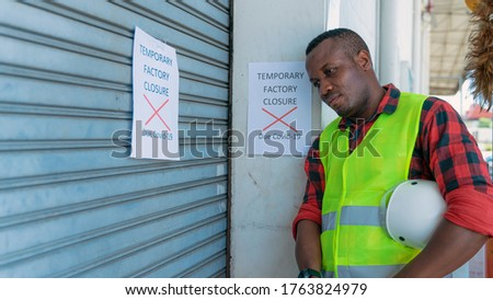 african american factory engineer at factory gate with annoucement of factory closed due to coronavirus covid-19 pandemic caused unemployment economics crisis and recession ストックフォト ©