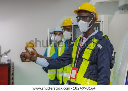 african american factory worker and team in uniform with safety vest and helmet wearing face mask for coronavirus protection thumb up together for teamwork in factory control room Foto stock ©