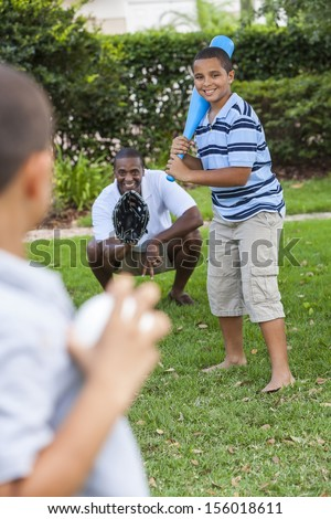 African American family, man, & boy children, father & two sons playing baseball together outside. stock photo