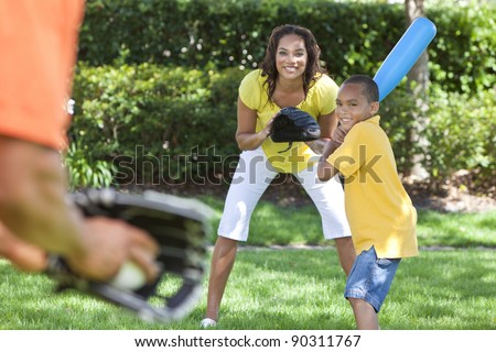 African American family, man, woman, boy child, mother, father, son playing baseball together outside. stock photo