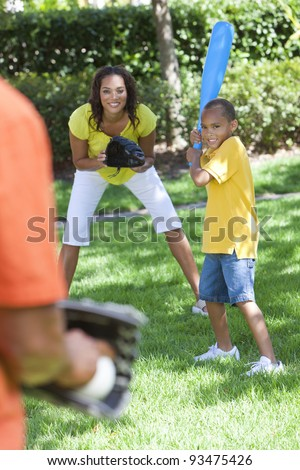 African American family, man, woman, boy child, mother, father, son playing baseball together outside.