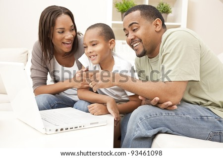 African American family, parents and son, having fun using a laptop computer together