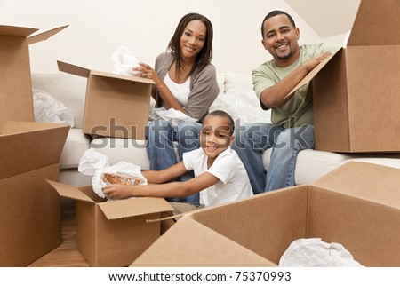 African American family, parents and son, unpacking boxes and moving into a new home, The adults are unpacking crockery, the child is unpacking a toy airplane. - stock photo