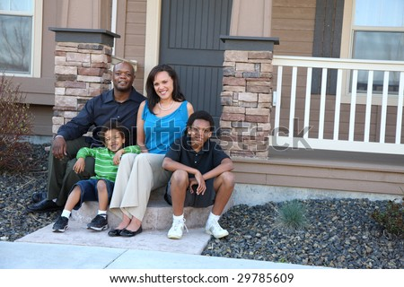 African American family sitting together on front steps of home