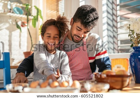 African american father and daughter cooking in the kitchen. Dad is wearing an apron. They are both smiling.