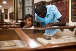African American father and daughter looking at stands with exhibits at historical museum