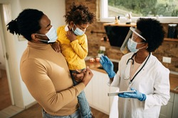 African American father and daughter talking to their family doctor who is visiting them at home during coronavirus pandemic. Focus is on doctor.