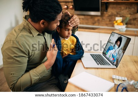 African American father and his sick daughter using laptop while having video call with family doctor during coronavirus pandemic. Focus is on daughter.