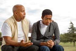 African American father and son in deep conversation.