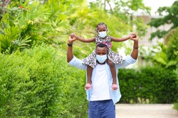 African American father gave piggyback ride to his little daughter and having a good time together walking around the neighborhood while wearing mask during social distancing and new normal for covid