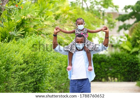 African American father gave piggyback ride to his little daughter and having a good time together walking around the neighborhood while wearing mask during social distancing and new normal for covid Photo stock ©
