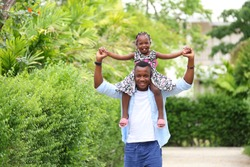African American father gave piggyback ride to his little daughter with happy mental health and having a good time together while walking outside the house around the neighborhood