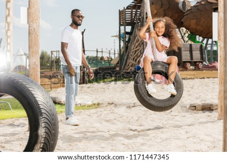 african american father standing near smiling daughter on tire swing at amusement park Imagine de stoc ©