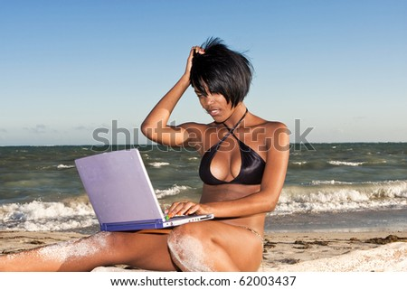 african-american female at beach on laptop  looking confused