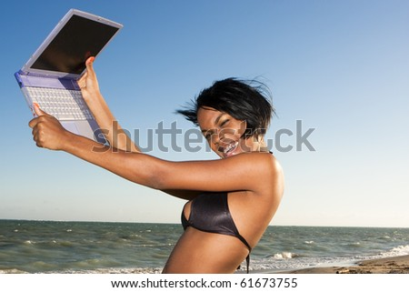 african-american female at the beach on laptop